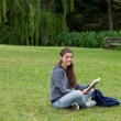 Smiling young adult reading a book while sitting cross-legged — Stock Photo #10328321