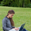 Serious young woman typing on her laptop while sitting cross-leg — Stock Photo