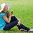 Young smiling girl sitting on the grass with a hat while holding — Stock Photo
