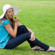 Young girl wearing a hat while sitting cross-legged and eating a — Stock Photo #10328362