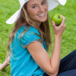 Attractive young woman sitting down while eating an apple — Stock Photo #10328365