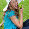 Happy young girl eating a green apple while sitting on the grass — Stock Photo #10328367