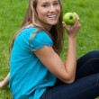 Smiling young woman holding a green apple while sitting in a par - Stock Photo