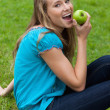 Stock Photo: Young smiling woman eating a green apple while sitting in a park