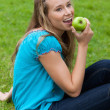 Smiling young girl eating a delicious green apple while sitting — Stockfoto