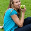 Smiling young girl eating a delicious green apple while sitting - ストック写真