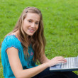 Young girl using her laptop in a park while looking at the camer — Stock Photo