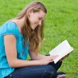 Happy young girl reading a book while sitting down in a park — Stock Photo #10328414