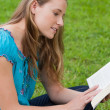 Young attractive girl sitting cross-legged in a park while readi — Stock Photo
