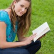 Young relaxed girl reading a book while sitting in the countrysi — Stock Photo