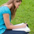 Serious young girl writing on her notebook while sitting on the — Stock Photo