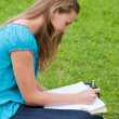 Stock Photo: Young happy girl doing her homework while sitting down on the gr