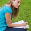 Attractive young girl sitting down in a park while doing her hom — Stock Photo #10328426
