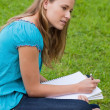 Attractive young girl sitting down in a park while doing her hom — Stock Photo