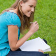 Young smiling girl looking towards the side while writing on her — Stock Photo