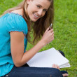 Young smiling student holding her pen while looking at the camer — Stock Photo