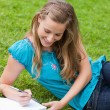 Stock Photo: Young smiling girl lying on the grass while writing on a noteboo