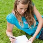 młoda dziewczyna poważne, leżąc na trawie w parku pisząc na — Zdjęcie stockowe #10328435