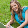 Stock Photo: Smiling teenage girl lying on the side while using her laptop