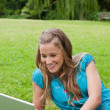 Young smiling girl lying down in a park while using her laptop — Stock Photo