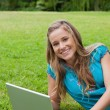 Young girl looking at the camera while using her laptop and smil — Stock Photo