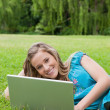 Young smiling girl using her laptop while lying on the grass — Stock Photo #10328460