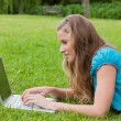 Side view of a young girl typing on her laptop while lying down — Stock Photo #10328462