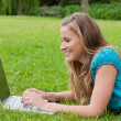 Young smiling girl looking at her laptop while lying down — Stock Photo