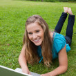 Smiling teenage girl looking at the camera while lying on the gr — Stock Photo #10328478