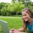 Young smiling girl using her laptop in a park while lying on the — Stock Photo