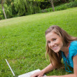 Smiling girl lying in a public garden while working on her lapto — Stock Photo #10328491