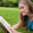Serious young woman reading a book while lying on the grass - Foto de Stock