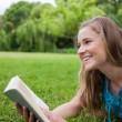 Young smiling woman lying in a parkland while holding a book — Stock Photo