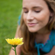 Yellow flower held by an attractive young woman - Stock Photo