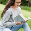 Young relaxed girl sitting on the grass in a park while reading — Stock Photo
