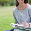 Smiling student doing her homework while sitting on the grass — Stock Photo