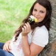 Young smiling woman smelling flowers while sitting against a tre — Stock Photo #10328686