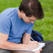 Young student sitting on the grass while writing on his notebook - Stock Photo