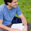 Young smiling man looking away while working on the grass — Stock Photo