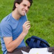 Young smiling man working while sitting on the grass — Stock Photo