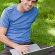 Young smiling man using his laptop while sitting cross-legged — Stock Photo
