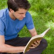 Stock Photo: Young serious man sitting cross-legged while reading a book