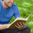 Stock Photo: Young smiling mreading book while siting on grass
