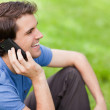 Young man talking on the phone while sitting on the grass — Stock Photo #10328772