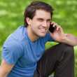 Young happy man using his mobile phone while sitting on the gras — Stock Photo #10328779