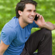 Young man laughing while sitting on the grass and talking on the — Stock Photo