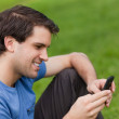 Young man sending a text with his cellphone while sitting on the — Stock Photo #10328788
