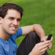 Happy young man looking at the camera while sending a text — Stock Photo #10328791