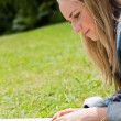 Young blonde girl lying on the grass while reading a book — Stock Photo