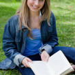 Young girl sitting cross-legged while holding a book and looking — Stock Photo
